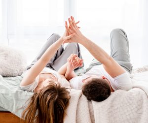 Beautiful young couple lying in the bed and hold hands of echa other in sunny room with panoramic window. Girl and guy wearing pajamas spend time together in the bedroom. Lovely family morning